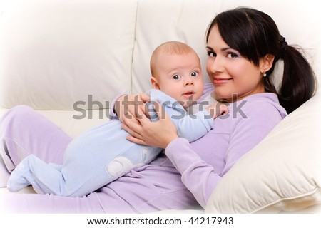 beautiful young mother holds a baby - stock photo