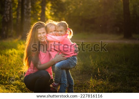 Beautiful young mother hugs her little daughters in the evening in the summer park on a background of sunset. Happy family.