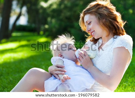 Beautiful young mother is feeding her baby from a bottle outdoor. Outdoor Portrait of happy family - stock photo