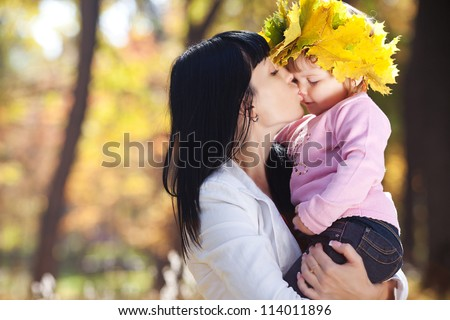 beautiful young mother kissing her daughter in autumn forest