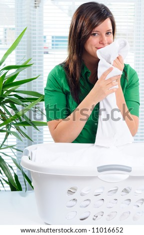 Beautiful Young Mother Smelling The Fresh Laundry Fabric - stock photo