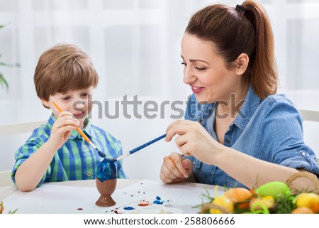 Beautiful young mother teach son how to paint easter eggs - stock photo