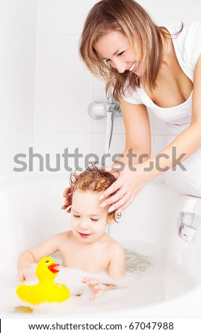 beautiful young mother washing her baby in the bath with foam (focus on the mother) - stock photo