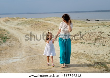 beautiful young mother with a child walking along the seashore - stock photo