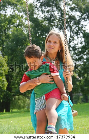 beautiful young mother with cute kid on swing - stock photo