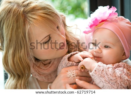 Beautiful young mother with her baby daughter - stock photo