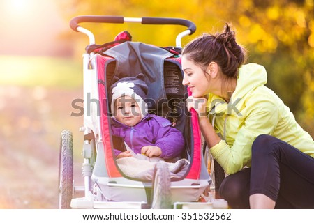 Beautiful young mother with her daughter in jogging stroller running outside in autumn nature - stock photo