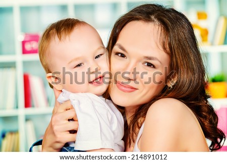 Beautiful young mother with her little baby at home. - stock photo