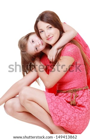 Beautiful young mother with her little daughter in pink dresses and hats hugging and smiling - stock photo