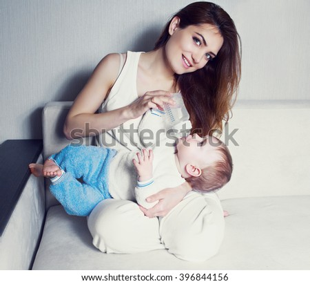 beautiful young mother with her one year old son at home