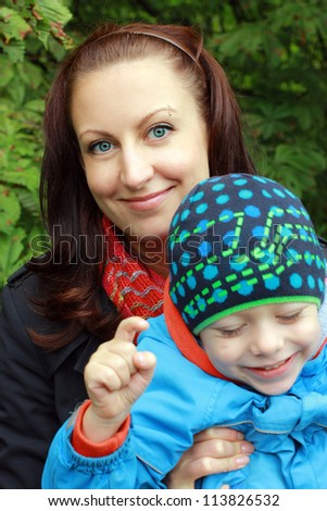 Beautiful young mother with her son outdoors - stock photo