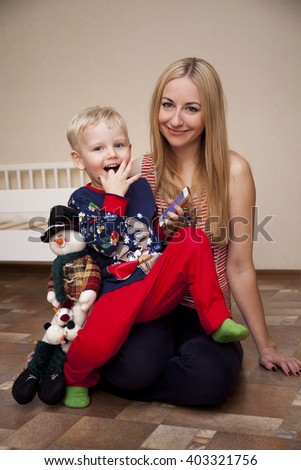 Beautiful young mother with little boy at home - stock photo