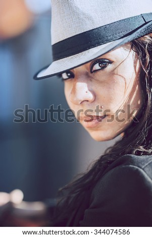 Beautiful young mulatto woman in urban environment - stock photo