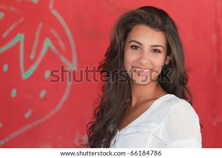 Beautiful young multicultural woman in an outdoor lifestyle pose with a red background.
