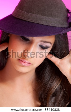 Beautiful young multicultural woman wearing a hat in a studio pose with purple background. - stock photo