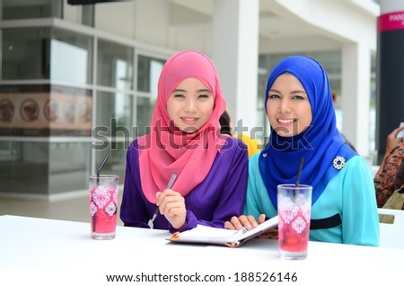 beautiful young muslim businesswoman sharing info and happy together