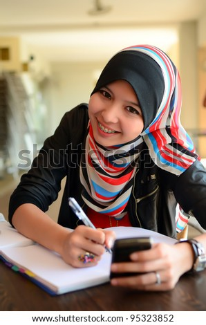 Beautiful young muslim  college girl with book and smile - stock photo