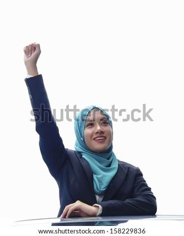 Beautiful young Muslim girl raises her hands isolated background - stock photo