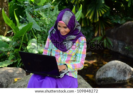 beautiful young Muslim girl sitting with notebook