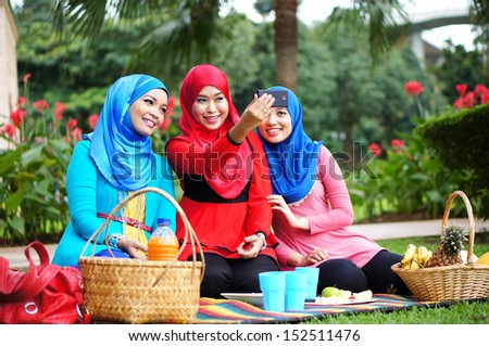 Beautiful Young Muslim Girls Taking Picture With Hand phone at park with happy face - stock photo