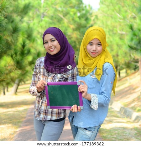 beautiful young muslim student smile with green board