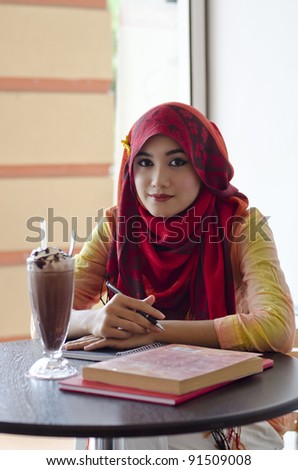 beautiful young muslim woman holding a pen and notebook during lunch at coffee shop - stock photo