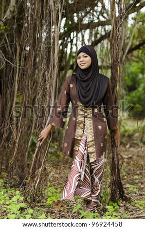Beautiful young Muslim women with brown traditional songket kebaya dress in the jungle