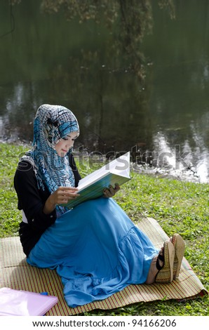beautiful young muslimah woman with stylish head scarf reading a book near the lake - stock photo