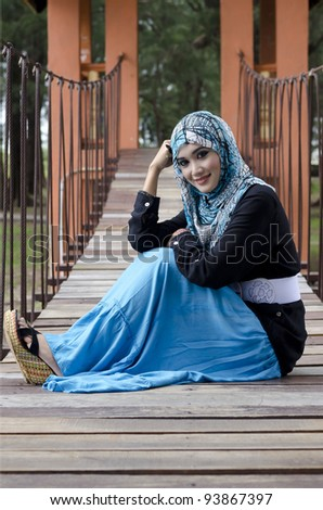 beautiful young muslimah women with stylish head scarf smiling sit on the hanging bridge at recreation park - stock photo
