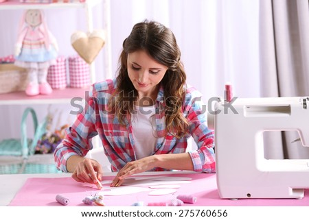 Beautiful young needlewoman in workshop - stock photo