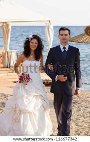 Beautiful young newlyweds couple walking on the beach - stock photo