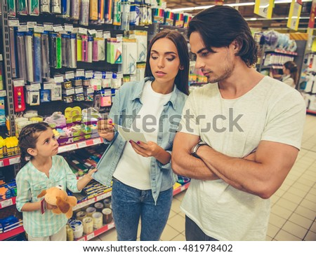 Beautiful young parents and their cute little daughter are choosing school stationery in the supermarket. Mom and dad are discussing the list