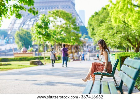 Beautiful young Parisian woman in long brown silk skirt sitting on the bench near the Eiffel tower on a summer day - stock photo