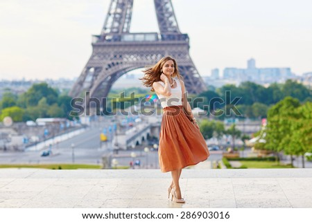 Beautiful young Parisian woman in long skirt near the Eiffel tower on a summer day - stock photo