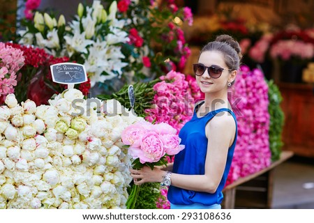 Beautiful young Parisian woman selecting pink peonies in French flower shop or at market - stock photo
