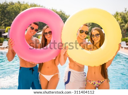 Beautiful young people having fun in swimming pool with colored rubber rings. - stock photo
