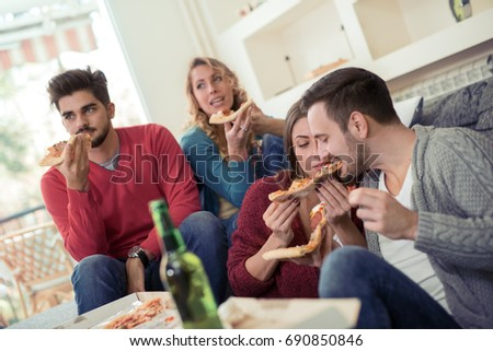 Beautiful young people in casual clothes are resting with pizza and bottles of drink, talking and smiling.
