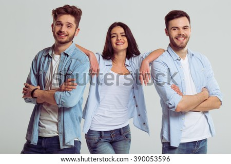 Beautiful young people in jeans are looking at camera and smiling, on a gray background. Woman is leaning on men - stock photo