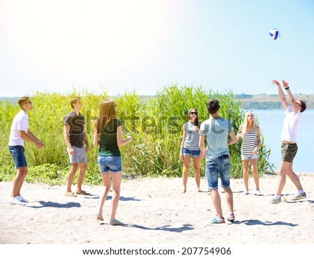 Beautiful young people playing volleyball on beach - stock photo