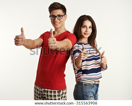 Beautiful young people showing thumb up. Attractive Caucasian couple gesturing, posing in studio. Advertisement concept.  - stock photo