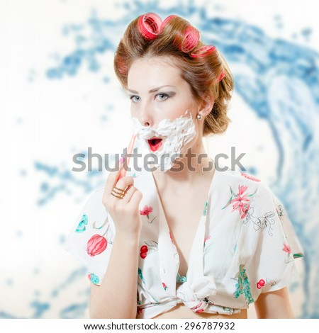 Beautiful young pinup woman shaving face with foam and razor looking in camera on bokeh background closeup portrait - stock photo