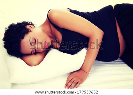 Beautiful young pregnant woman lying on bed - stock photo