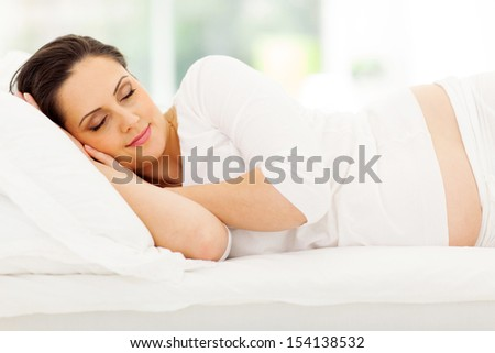 beautiful young pregnant woman sleeping peacefully in bed - stock photo