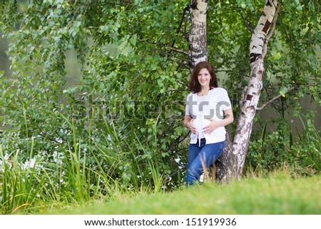 Beautiful young pregnant woman walking in a park next to a river
