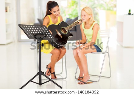 beautiful young preteen girl having guitar lesson at home - stock photo