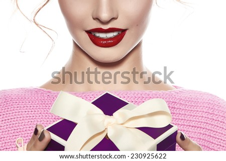 Beautiful young pretty girl with a bright evening make-up of shiny red lipstick on the lips blond blonde curly hair festive mood knitted sweater winter Christmas New Year and birthday gift surprise - stock photo