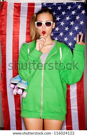 beautiful young pretty woman in sunglasses with national usa flag in background, sucking a lollipop - stock photo