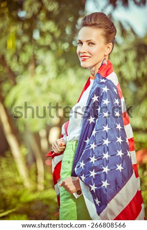 Beautiful young pretty woman with national usa flag over green natural background. soft toned image