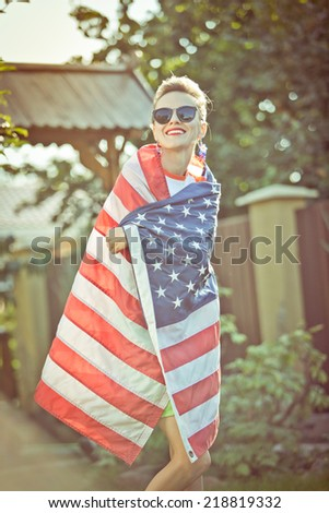 Beautiful young pretty woman with national usa flag over sunshine. soft backlight - stock photo