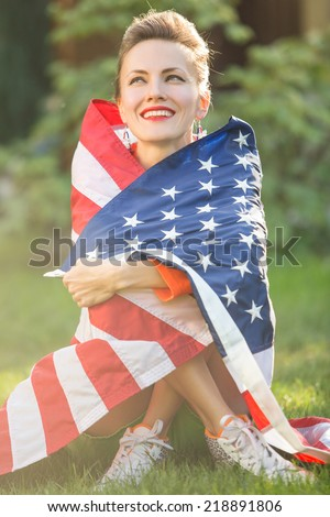 Beautiful young pretty woman with national usa flag over sunshine. soft backlight